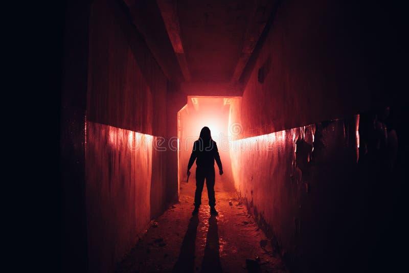 Siluetta terrificante con il coltello nella costruzione abbandonata illuminata rosso scuro Orrore circa il concetto del maniaco fotografie stock libere da diritti