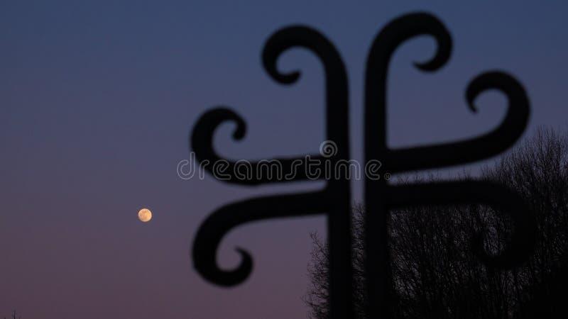 Siluetta trasversale ed il cielo con la luna piena fotografia stock