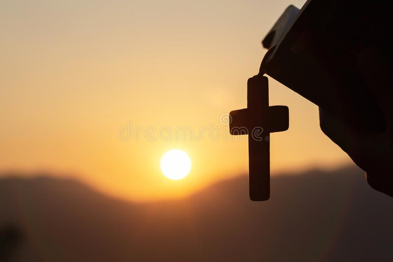 Siluette της χριστιανικής γυναίκας που κρατά μια Βίβλο και ένα ξύλινο χριστιανικό διαγώνιο περιδέραιο προσευμένος στο Θεό στοκ φωτογραφίες