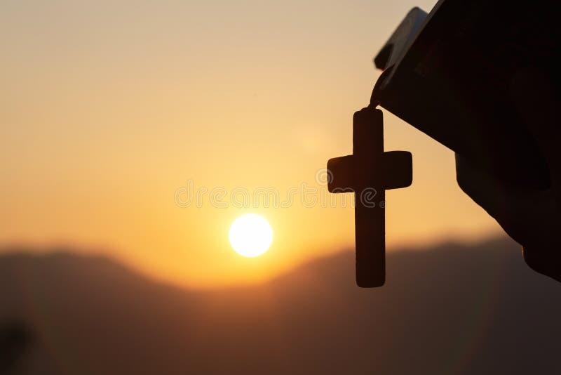 Siluette av den kristna kvinnan som rymmer en bibel och en träkristen arg halsband, medan be till guden arkivfoton