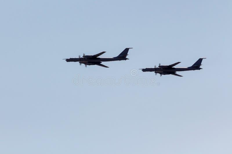 Siluette che pilotano i bombardieri strategici del turbopropulsore russo Tu-95 contro il cielo fotografia stock libera da diritti