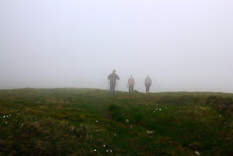 Siluette degli uomini in nebbia Escursione di viaggio degli uomini in montagne fotografie stock libere da diritti