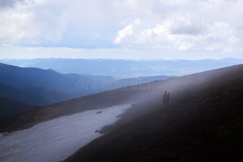 Siluette degli uomini in nebbia Escursione di viaggio degli uomini in montagne immagine stock