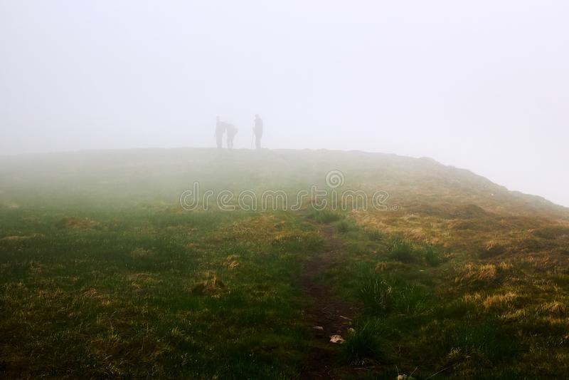 Siluette degli uomini in nebbia Escursione di viaggio degli uomini in montagne fotografie stock