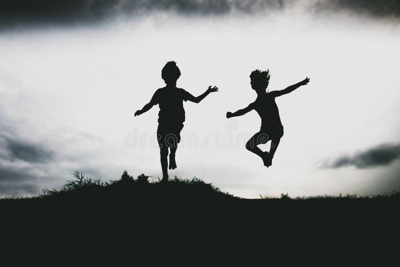 Siluette dei bambini che saltano da una scogliera della sabbia alla spiaggia fotografie stock