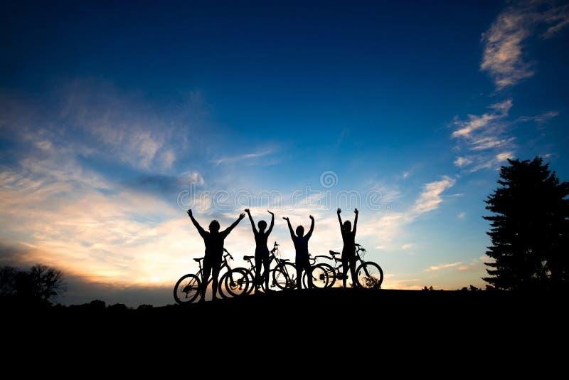 Siluette dei ciclisti al fondo del cielo di tramonto fotografia stock libera da diritti