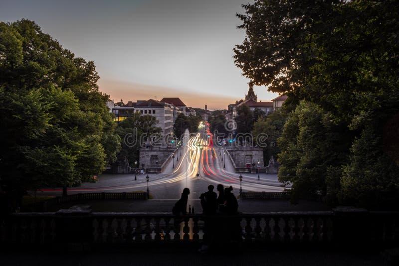 Siluette dei giovani che guardano il tramonto a Monaco di Baviera a GER immagini stock