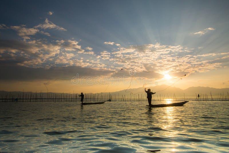 Siluette dei pescatori tradizionali che gettano rete da pesca du fotografia stock libera da diritti