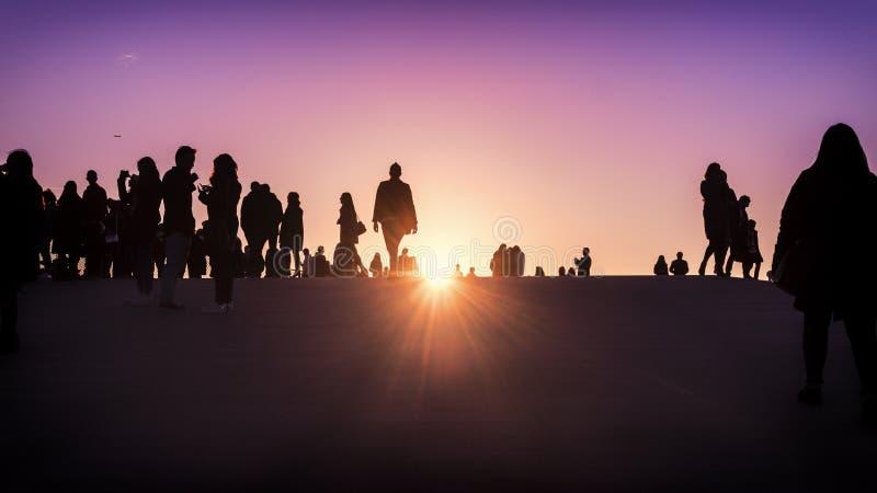 Siluette del gruppo di persone che guardano insieme il tramonto fotografie stock