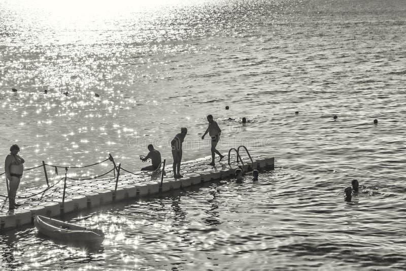 Siluette del sole luminoso di estate backlit la gente immagini stock libere da diritti