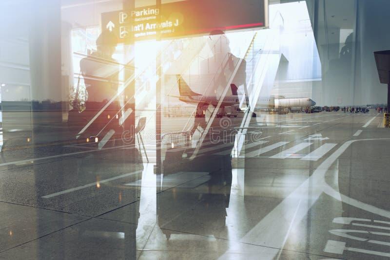 Siluette dell'uomo d'affari all'aeroporto che aspetta l'imbarco Doppia esposizione fotografie stock