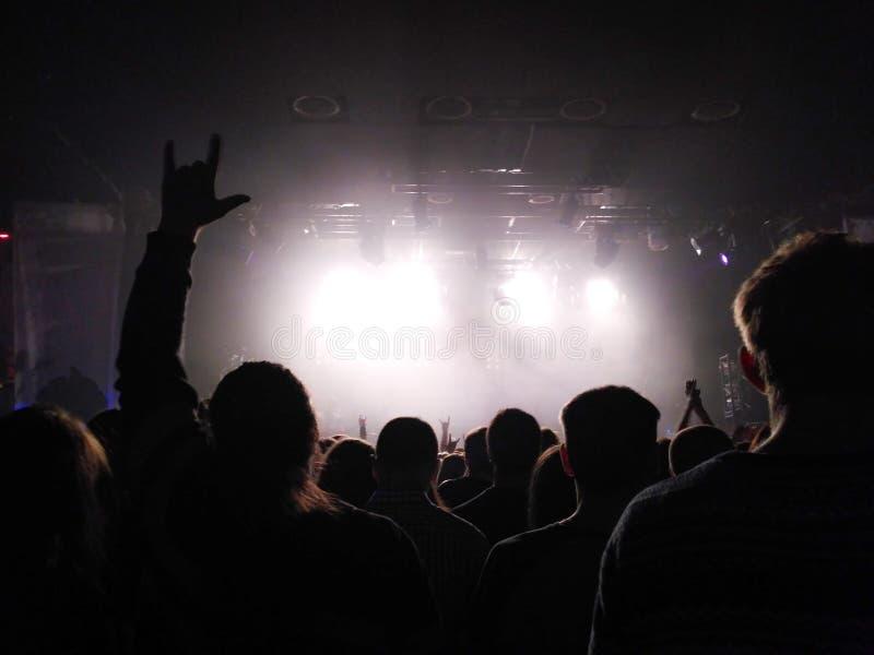 Siluette della gente ad un concerto Concerto di schiocco Rockband Il tipo fa una capra a mano Luce intensa sulla fase immagine stock