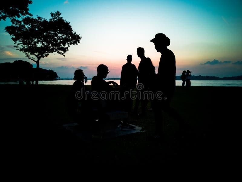 Siluette della gente ad una spiaggia immagine stock libera da diritti