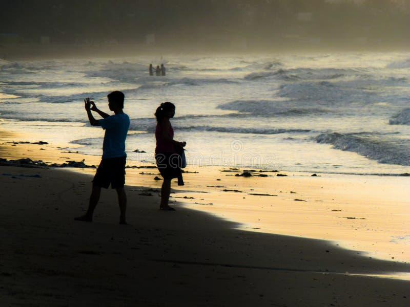 Siluette della gente ad una spiaggia fotografia stock libera da diritti