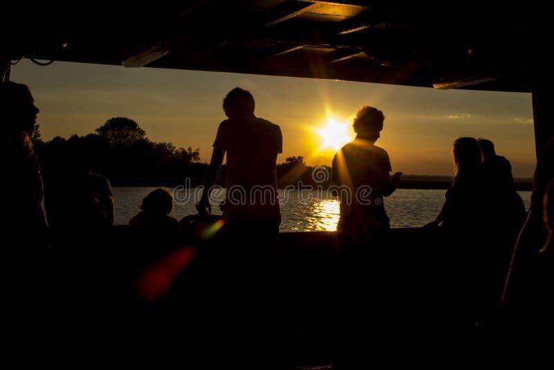 Siluette della gente al tramonto Viaggio di sera all'isola fotografia stock