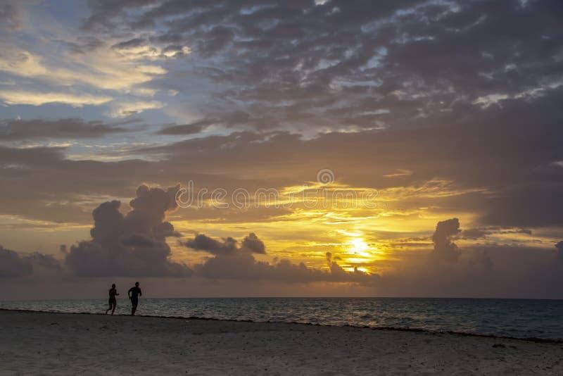 Siluette della gente che corre lungo la spiaggia fotografie stock libere da diritti