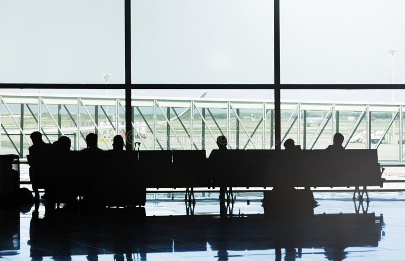 Siluette della gente che si siede sulle sedie di un aeroporto che aspetta il loro volo fotografia stock libera da diritti