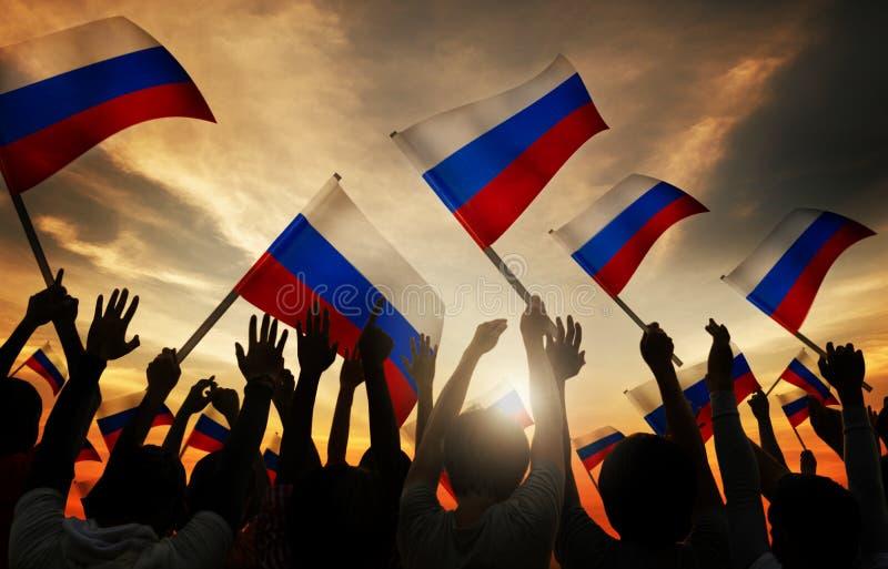 Siluette della gente che tiene bandiera della Russia fotografia stock libera da diritti