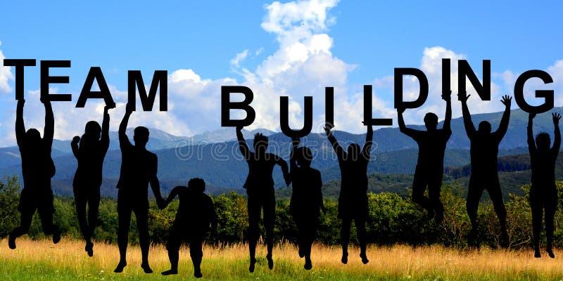 Siluette della gente che tiene le lettere con il TEAM-BUILDING immagini stock