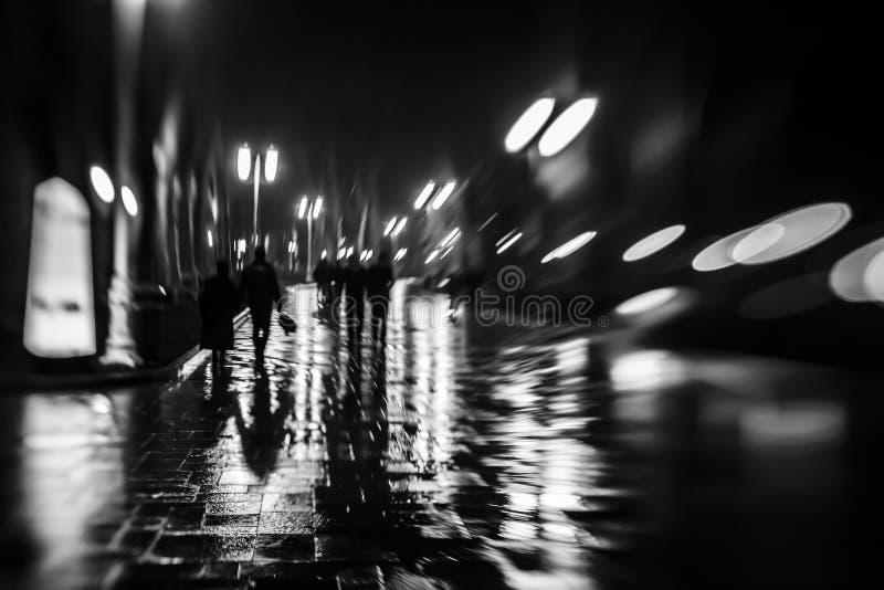 Siluette della gente come lo zombie che cammina alla notte nel piovoso alla luce delle lampade di via, fuoco vago molle fotografia stock libera da diritti