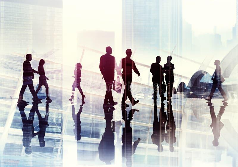 Siluette della gente di affari che cammina dentro l'ufficio fotografia stock libera da diritti