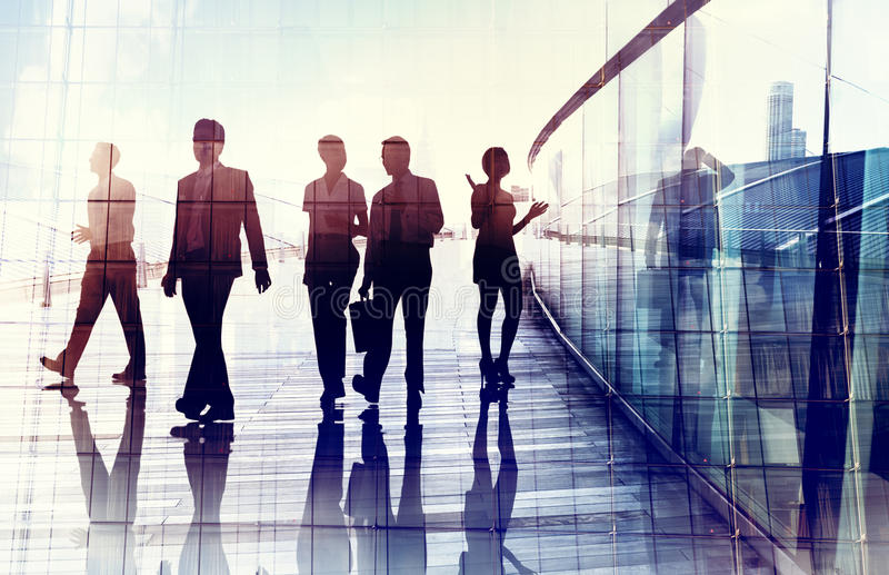 Siluette della gente di affari che cammina nell'ufficio immagini stock libere da diritti