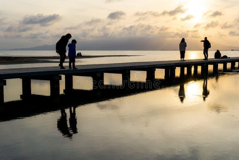Siluette della gente irriconoscibile su un pilastro al tramonto fotografie stock libere da diritti
