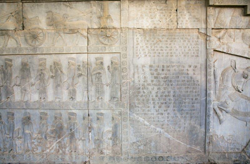 Siluette della gente storica sul bassorilievo di pietra distrutto in Persepolis fotografia stock libera da diritti