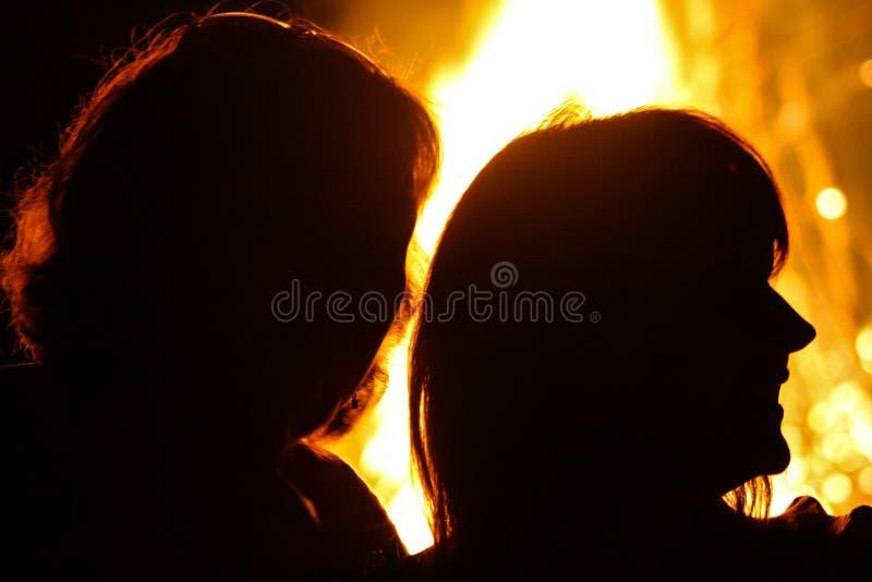 Siluette della gente su un fondo del fuoco fotografia stock