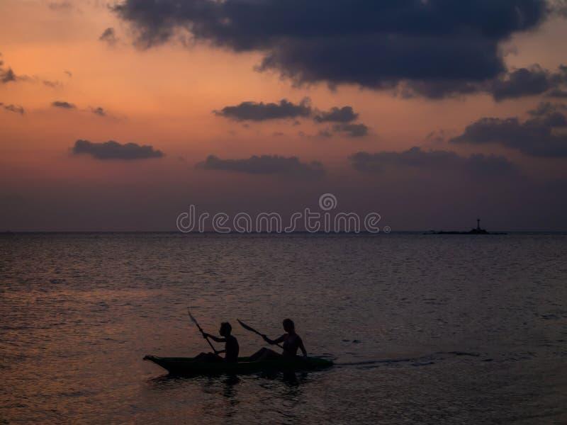 Siluette della gente in un kajak nei raggi del tramonto contro lo sfondo delle nuvole fotografie stock libere da diritti