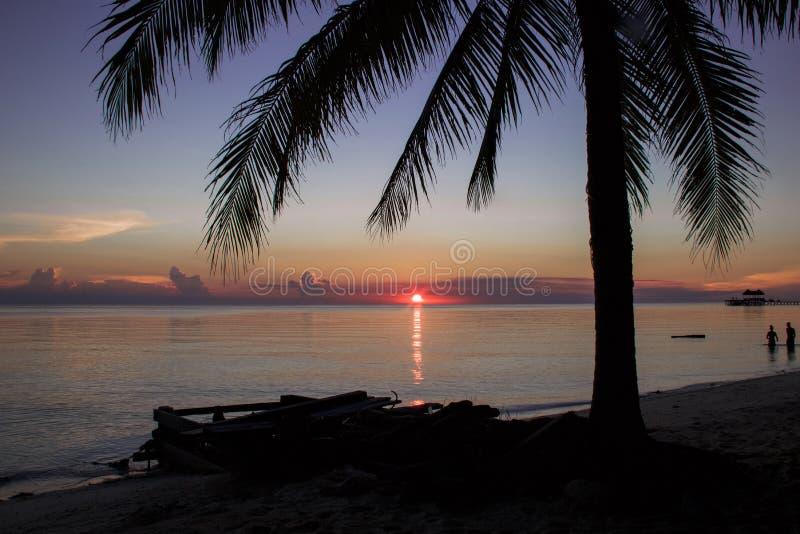 Siluette della palma e della gente nella vista sul mare e nel tramonto esotici immagini stock libere da diritti