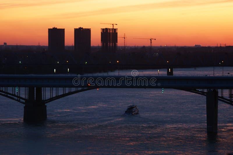 Siluette delle case in costruzione e del ponte del fiume fotografia stock