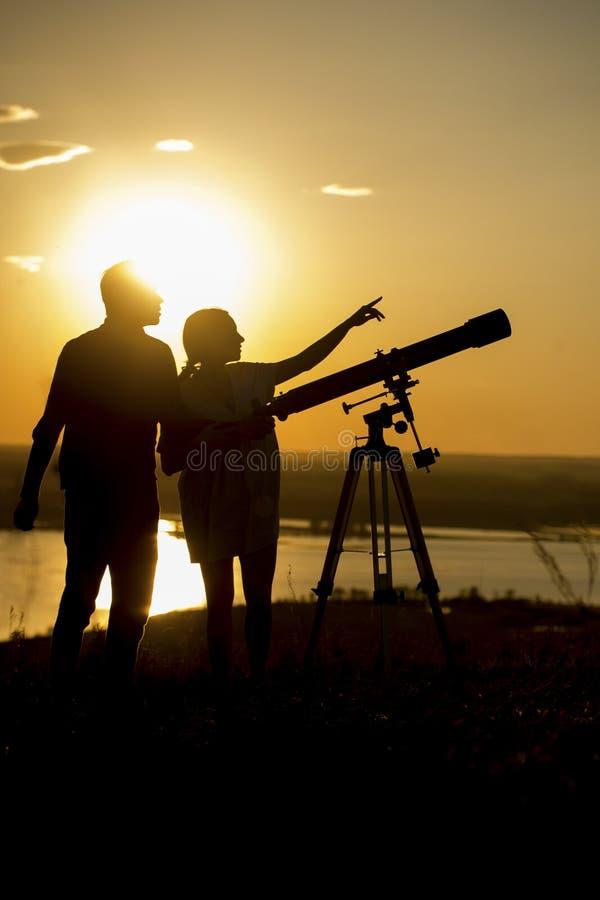 Siluette delle coppie che guardano tramite il telescopio sulla collina a fotografie stock libere da diritti