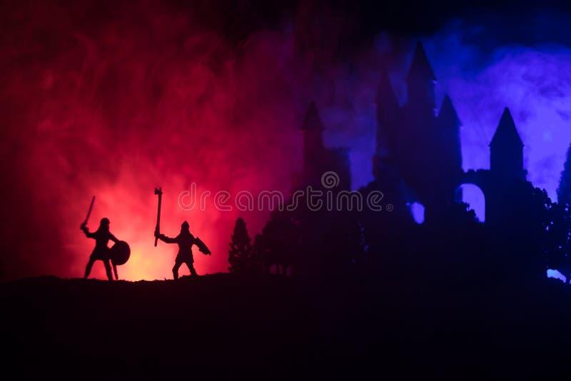 Siluette delle figure come oggetti separati, lotta fra i guerrieri su fondo nebbioso tonificato scuro con il vecchio castello got fotografie stock