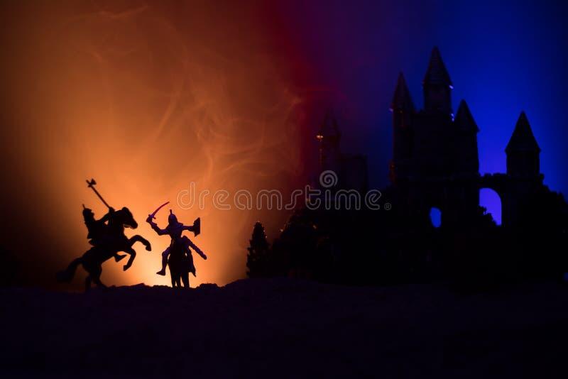 Siluette delle figure come oggetti separati, lotta fra i guerrieri su fondo nebbioso tonificato scuro con il vecchio castello got fotografia stock libera da diritti