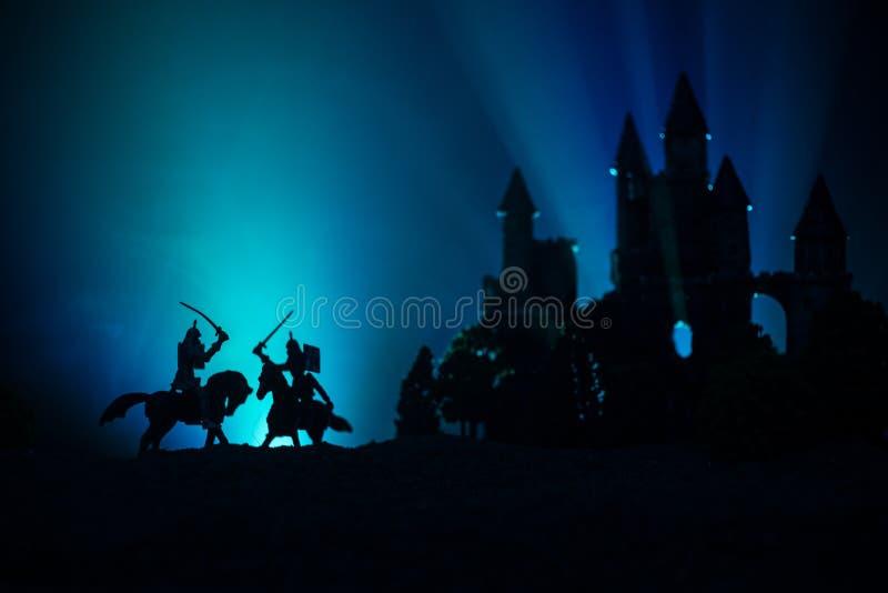 Siluette delle figure come oggetti separati, lotta fra i guerrieri su fondo nebbioso tonificato scuro con il vecchio castello got fotografie stock libere da diritti