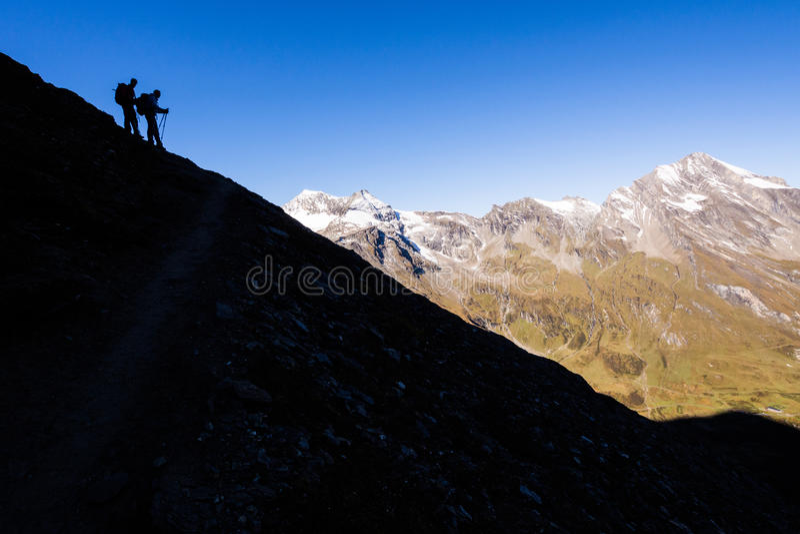 Siluette delle viandanti nelle montagne fotografia stock