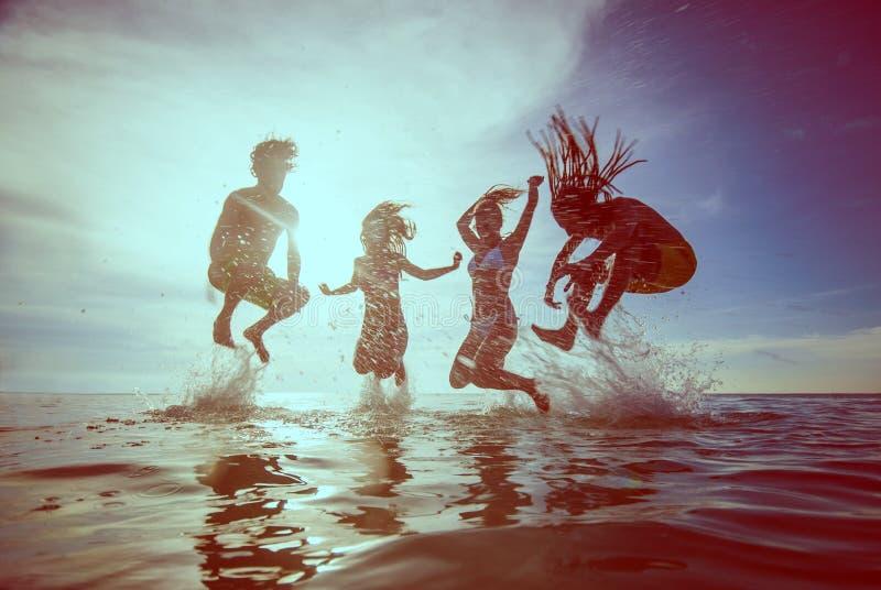 Siluette di estate dei giovani felici che saltano nel mare sulla b immagini stock libere da diritti