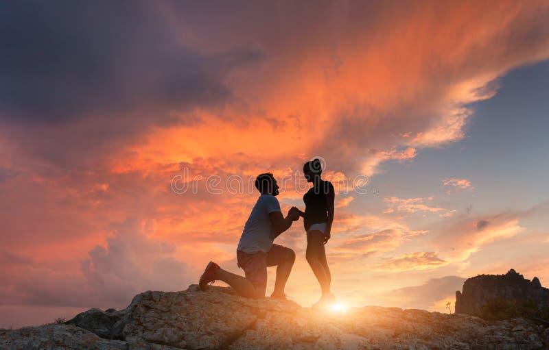 Siluette di un uomo che presenta proposta di matrimonio alla sua amica fotografie stock