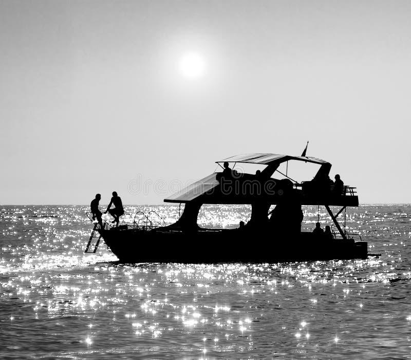 Siluette di una barca e di una gente di mare che riposano su  fotografie stock libere da diritti