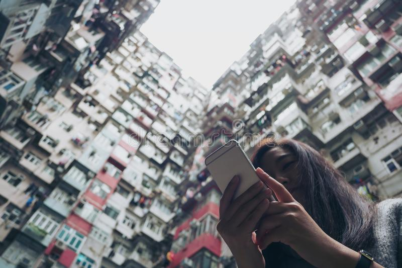 Siluette ed immagine di angolo basso di una donna che utilizza telefono cellulare con un edificio residenziale ammucchiato nella  immagini stock libere da diritti