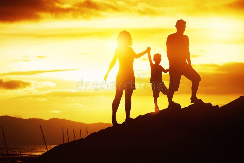 Siluette felici di divertimento della spiaggia di tramonto della famiglia fotografie stock libere da diritti
