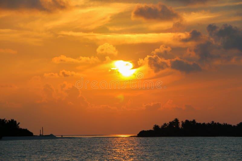 Siluette scure delle palme e del cielo nuvoloso stupefacente sul tramonto all'isola tropicale nelle isole delle Maldive immagini stock
