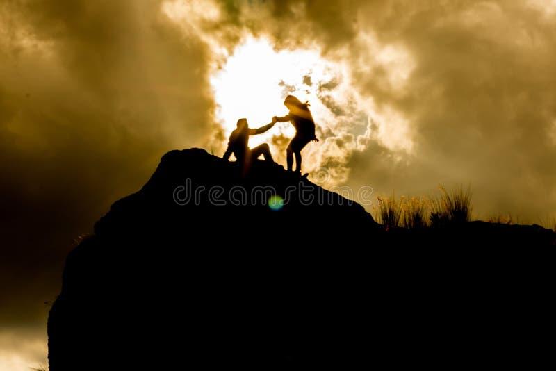Siluette sopra una montagna fotografia stock