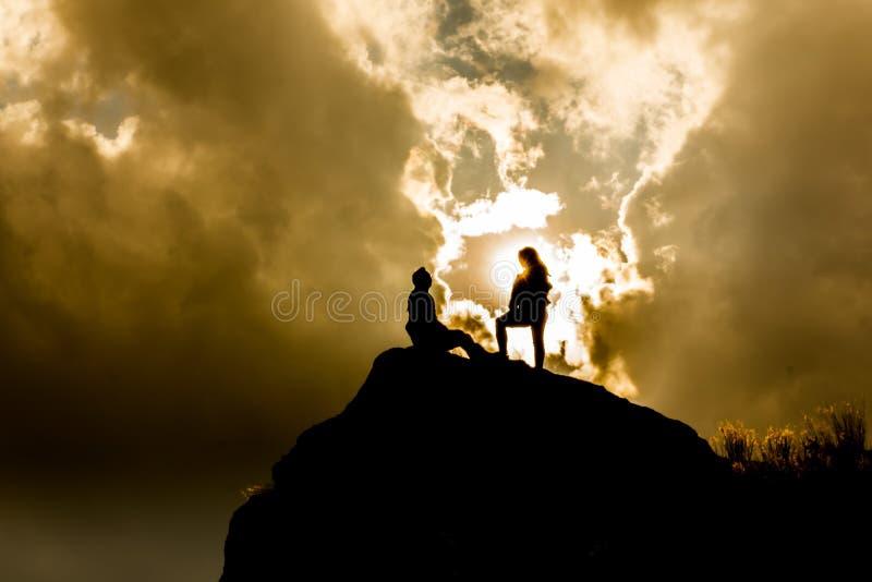 Siluette sopra una montagna fotografie stock