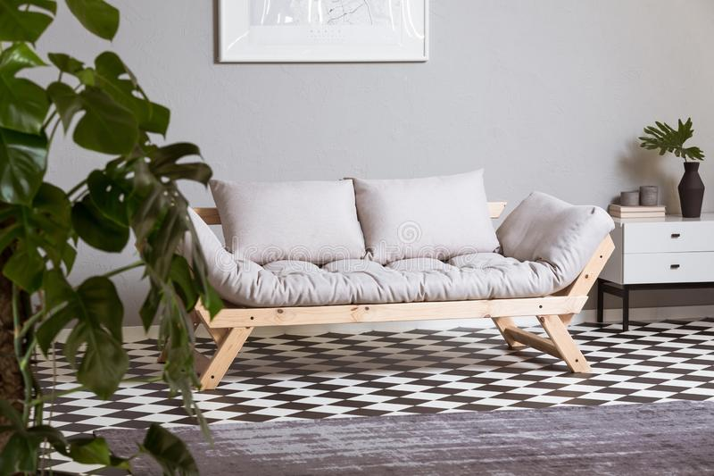 Silver abstract painting on grey wall above scandinavian futon stock images