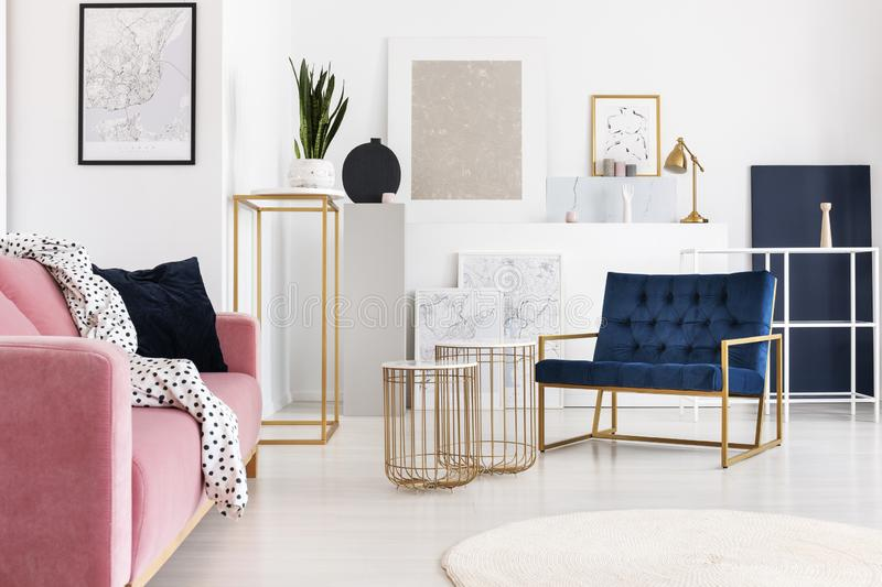 Silver painting on the wall of trendy living room with two elegant coffee tables, petrol blue armchair and powder pink. Silver abstract painting on the wall of royalty free stock image