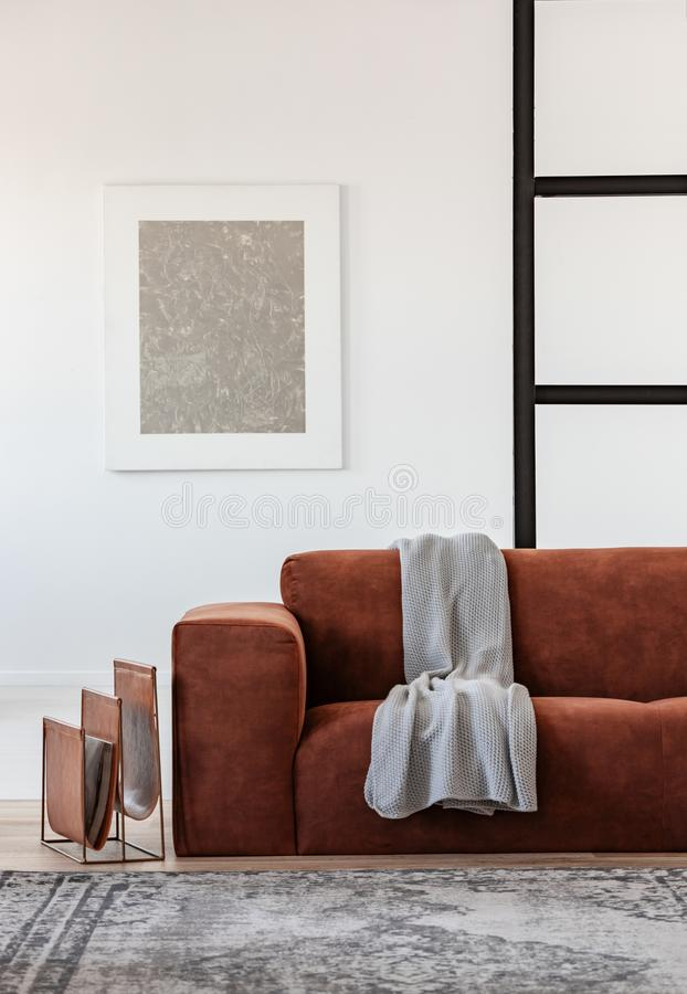 Silver abstract painting in white frame on the wall of trendy living room interior with brown corner sofa. Silver abstract painting in white frame on the wall of stock photo
