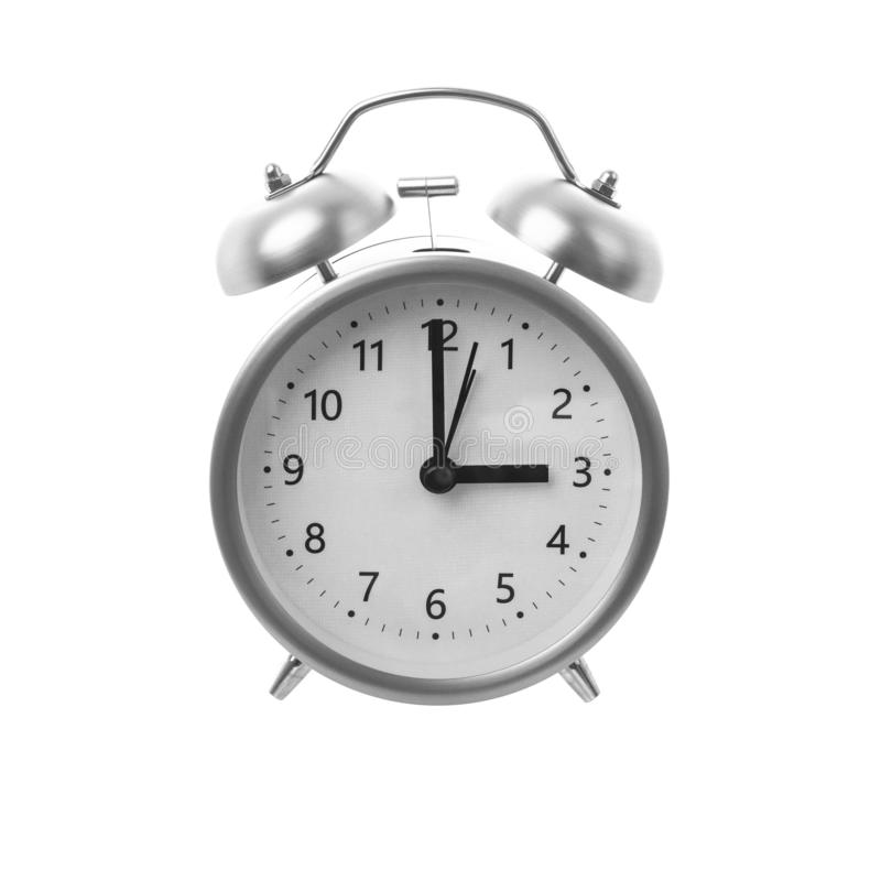 Silver Alarm Clock on a white background. With the time set to 3 O`clock stock image