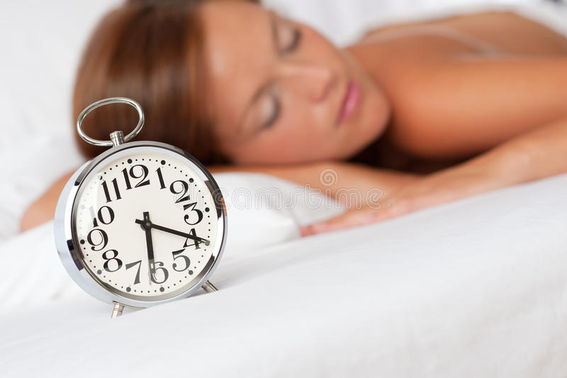Silver alarm clock on white bed royalty free stock photography